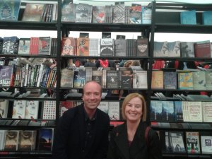 Laurence and Steph Patteson kneeling below 20 Crooked Cat titles!
